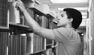 This undated photo provided by Occidental College shows former president Barack Obama in Occidental College's Clapp Library in Los Angeles. California's Occidental College, where Obama studied from 1979 to 1981, is offering scholarships in honor of the former president. The school in Los Angeles announced Wednesday, Sept. 27, 2017 that the Barack Obama Scholars Program will launch in the fall of 2018. (Thomas Grauman/Occidental College via AP)