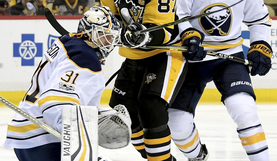 Buffalo Sabres goalie Chad Johnson makes a save on Pittsburgh Penguins' Sidney Crosby during the first period of an NHL hockey game, Wednesday Sept. 27, 2017,  in Pittsburgh. (Peter Diana/Pittsburgh Post-Gazette via AP)