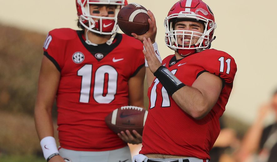 FILE - In this Saturday, Sept. 23, 2017, file photo, injured Georgia quarterback Jacob Eason, left, watches as Jake Fromm warms up for the team's NCAA college football game against Mississippi State in Athens, Ga. Georgia freshman Jake Fromm has played so well in place of the injured Jacob Eason that the seventh-ranked Bulldogs must decide what to do once Eason is healthy again. (Curtis Compton/Atlanta Journal-Constitution via AP, File)
