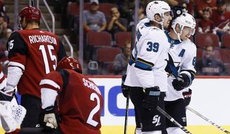 "FILE - San Jose Sharks' Mikkel Boedker, right, celebrates his second goal of the night with teammate Logan Couture (39) as Arizona Coyotes' Luke Schenn (2) and Brad Richardson (15) pause on the ice during the first period of a preseason NHL hockey game in Glendale, Ariz. With most of the same players back who helped San Jose make it to the Stanley Cup Final two seasons ago, the Sharks believe they still have the pieces in place to make another run at the Stanley Cup. ""Guys have got to step up,"" Couture said. (AP Photo/Ross D. Franklin, File)"