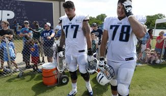 FILE - In this Aug. 4, 2016 file photo, Tennessee Titans offensive lineman Taylor Lewan (77) and Jack Conklin (78) take a break during NFL football training camp in Nashville, Tenn. The Titans are tied for first in the NFL giving up only two sacks through the first three weeks, and they've got the league's second-best rushing attack. Their next test comes Sunday in a visit to Houston against J.J. Watt and the Texans.. (AP Photo/Mark Zaleski, File)