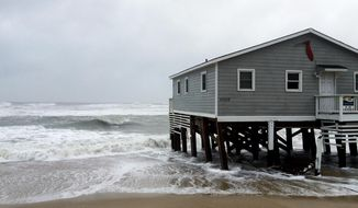 Waves wash ashore hitting a house as winds and storm surge from Tropical Storm Maria lash North Carolinas Outer Banks as the storm moves by well off-shore on Wednesday, Sept. 27, 2017. Dare County officials said the high tide flooded some roads in the area and travel is hazardous. (AP Photo/Ben Finley)
