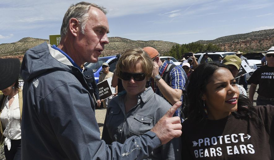"""FILE--In this May 8, 2017, file photo, Interior Secretary Ryan Zinke argues with pro monument activist Cassandra Begay after she directed pointed questions regarding his failure to meet with more Native Americans during his tour of Bears Ears National Monument in southeastern Utah. Zinke has closely followed his boss' playbook, encouraging mining and drilling on public lands and size reductions for national monuments that President Donald Trump said were part of a """"massive land grab."""" Yet Zinke's made an exception in his home state of Montana. (Francisco Kjolseth/The Salt Lake Tribune via AP, file)"""