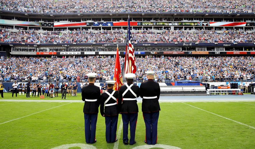 The American flag is presented before an empty players' bench before an NFL football game between the Titans and the Seattle Seahawks. Neither team came onto the field for the national anthem. (Associated Press)