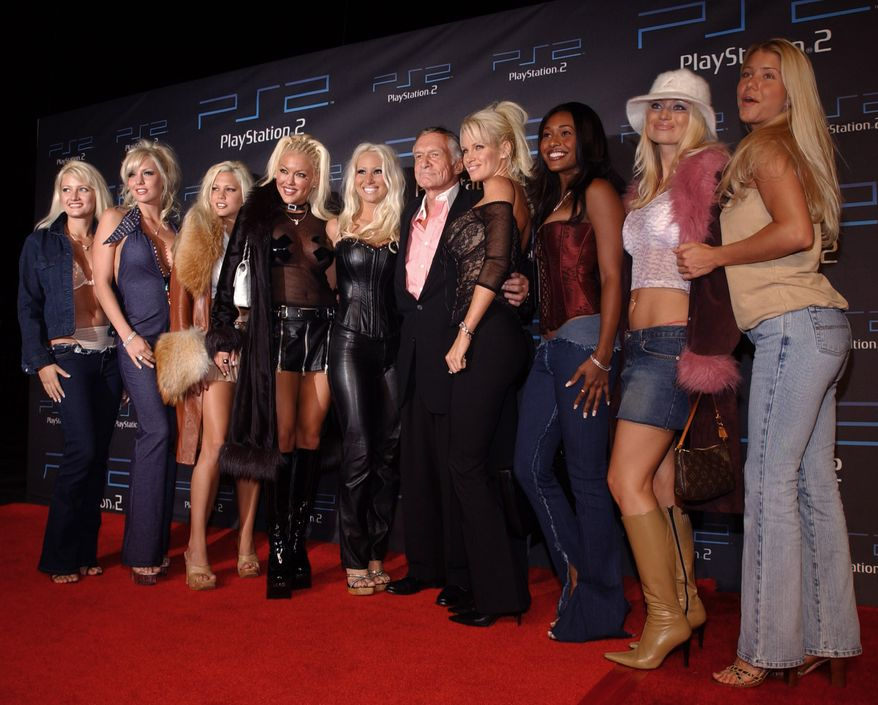 "Playboy Magazine founder Hugh Hefner, center, and his ""girlfriends"" arrive at the Sony Playstation 2 one-year anniversary party Thursday, Oct. 18, 2001 at the St. Regis Hotel in the Century City section of Los Angeles.  (AP Photo/Chris Weeks)"
