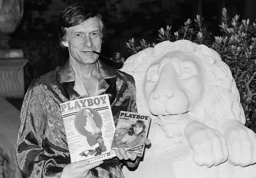 Playboy magazine publisher Hugh Hefner holds a copy of the magazine and a video cassette from the Playboy Channel, an all-night cable television venture Playboy Enterprises has undertaken, during an interview at the Playboy mansion in the Holmby Hills, Nov. 29, 1982, Los Angeles, Calif. (AP Photo/Nick Ut)