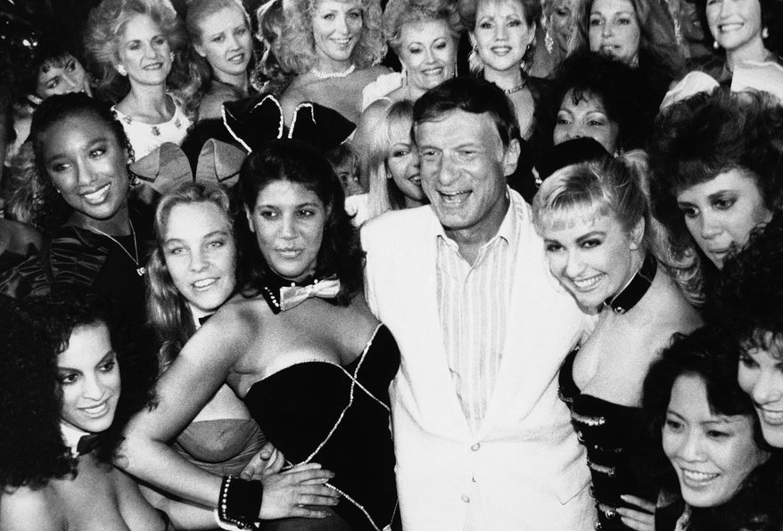 Hugh Hefner, center, poses with a group of current and former Playboy bunnies at the Playboy Club, Tuesday, June 25, 1986, Los Angeles, Calif. The famed clubs owned by the Playboy Corporation will be closing their doors on Monday, June 30. A few franchised clubs in the U.S. and abroad will remain open. The bunnies are unidentified. (AP Photo)
