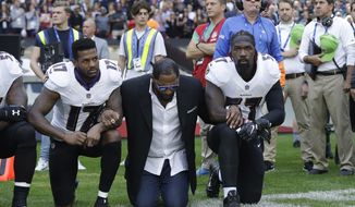 FILE - In this Sunday Sept. 24, 2017, file photo, Baltimore Ravens wide receiver Mike Wallace, from left, former player Ray Lewis and inside linebacker C.J. Mosley lock arms and kneel down during the playing of the U.S. national anthem before an NFL football game against the Jacksonville Jaguars at Wembley Stadium in London. People have signed an online petition asking for the removal of a statute of Lewis after he joined other NFL players kneeling during the national anthem. (AP Photo/Matt Dunham, File)