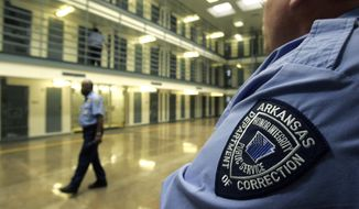 In this Aug. 10, 2009, file photo, guards patrol a cell block housing disruptive inmates at the Cummins Unit of the Arkansas Department of Correction near Varner, Ark. (AP Photo/Danny Johnston, File)