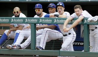 Texas Rangers' Rougned Odor, from left, Robinson Chirinos, Adrian Beltre, Drew Robinson and Phil Gosselin watch play against the Houston Astros from the top of the dugout in the ninth inning of a baseball game, Wednesday, Sept. 27, 2017, in Arlington, Texas. The Astros won 12-2. (AP Photo/Tony Gutierrez)