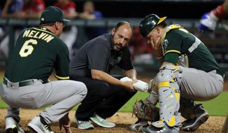 Oakland Athletics manager Bob Melvin (6) and trainer Nick Paparesta, center, check on catcher Bruce Maxwell after Maxwell was hit on the mask by a fouled ball off the bat of Texas Rangers' Ryan Rua in the fourth inning of a baseball game, Thursday, Sept. 28, 2017, in Arlington, Texas. Maxwell continued playing in the game. (AP Photo/Tony Gutierrez)