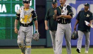 Oakland Athletics catcher Bruce Maxwell (13) and starting pitcher Sean Manaea, right front, walk from the bullpen for the first inning of a baseball game against the Texas Rangers  Thursday, Sept. 28, 2017, in Arlington, Texas. (AP Photo/Tony Gutierrez)
