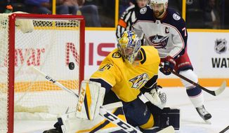 Nashville Predators goalie Pekka Rinne (35) turns the puck away, next to Columbus Blue Jackets winger Nick Foligno (71) during the first period of an NHL hockey preseason game Thursday, Sept. 28, 2017, in Nashville, Tenn. (AP Photo/Mike Strasinger)