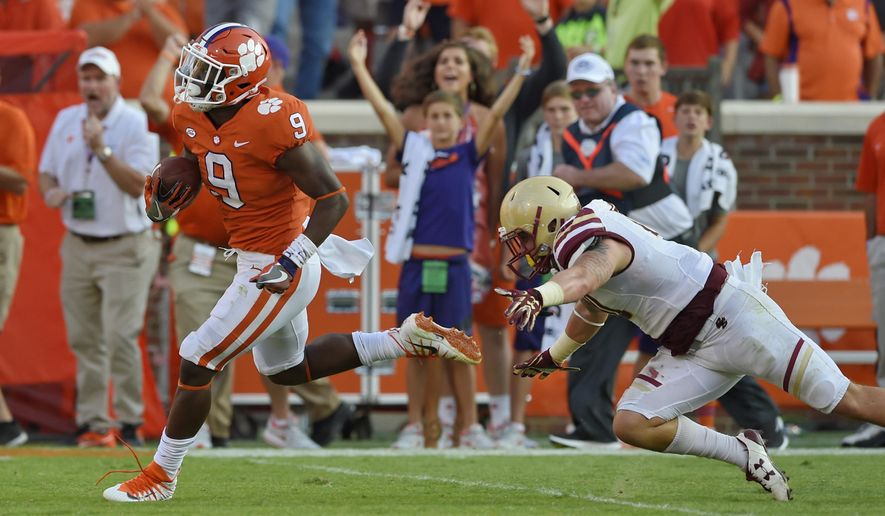 FILE - In this Saturday, Sept. 23, 2017, file photo, Clemson freshman running back Travis Etienne avoids the tackle by Boston College's Ty Schwab enroute to a 50 yard touchdown run during the second half of an NCAA college football game in Clemson, S.C. Etienne has everything a tailback needs. He''s got the speed as evidenced by his 81 and 50 yard TD runs the past two weeks. also has power moves, as he when picked Clemson over his home state school, LSU.  (AP Photo/Richard Shiro, File)