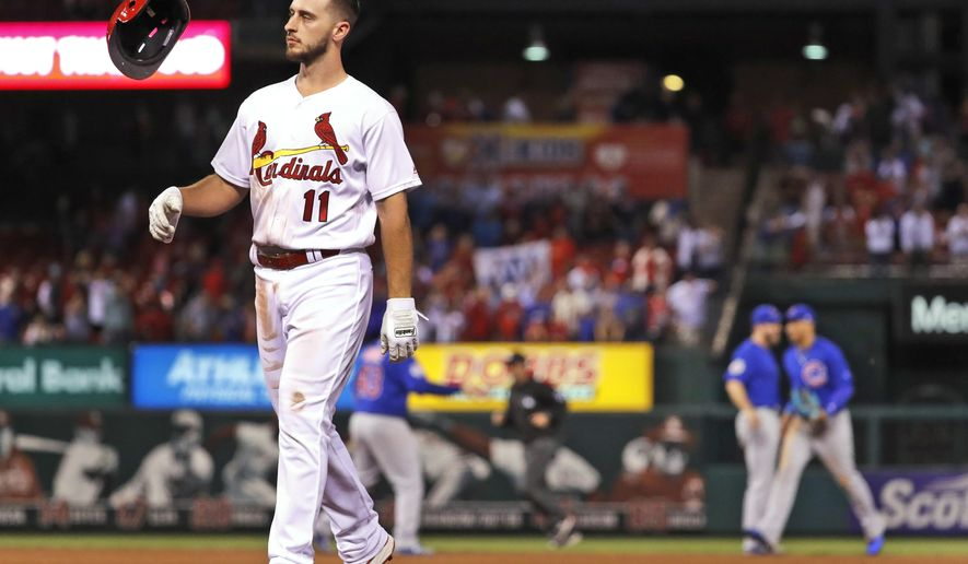 St. Louis Cardinals' Paul DeJong flips his helmet as he walks off the field after flying out to end a baseball game as members of the Chicago Cubs celebrate in the background Thursday, Sept. 28, 2017, in St. Louis. The Cubs won 2-1. (AP Photo/Jeff Roberson)
