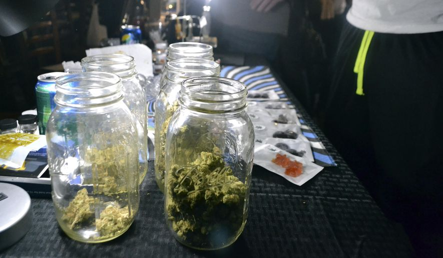 """In this Sept. 11, 2017, photo, jars of marijuana buds are displayed in Washington at a closed Ethiopian restaurant at a """"gifted"""" marijuana event. In the so-called """"District of Cannabis"""" it's legal to grow and consume marijuana, but illegal to buy or sell it. The result of this unique legal grey area has spawned a thriving cottage industry of businesses using the """"gifting"""" loophole. So far the city government and police are letting it happen. (AP Photo/P. Solomon Banda) **FILE**"""