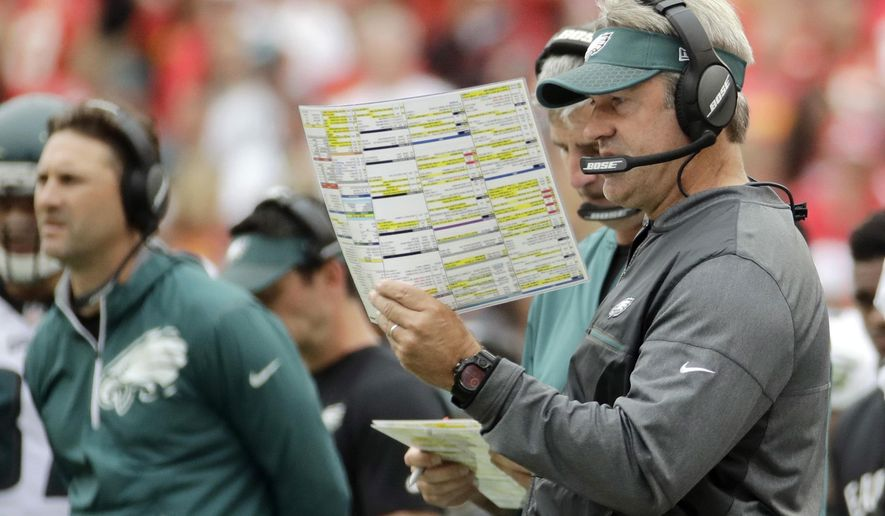 FILE - In this Sept. 17, 2017, file photo, Philadelphia Eagles head coach Doug Pederson consults his charts during the first half of an NFL football game against the Kansas City Chiefs in Kansas City, Mo. For better or worse, Pederson is aggressive. The second-year coach goes for it on fourth down more than anyone else in the NFL since he joined the Philadelphia Eagles last year. (AP Photo/Charlie Riedel, File)