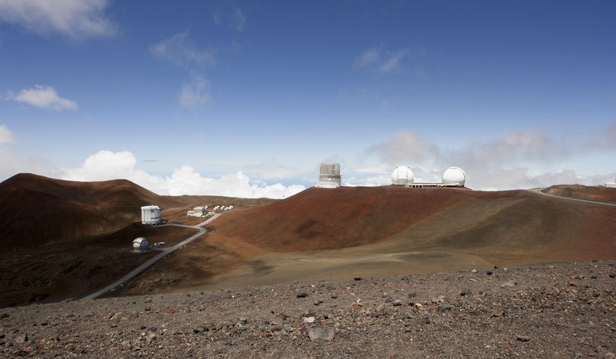 FILE - This Aug. 31, 2015, file photo shows telescopes on the summit of Mauna Kea on Hawaii's Big Island. Hawaii's land board on Thursday, Sept. 28, 2017, granted a construction permit for a giant telescope on a mountain that Native Hawaiians consider sacred, a project that has divided the state. The $1.4 billion Thirty Meter Telescope has pitted people who say the instrument will provide educational and economic opportunities against those who say it will desecrate the state's tallest mountain, called Mauna Kea. (AP Photo/Caleb Jones, File)