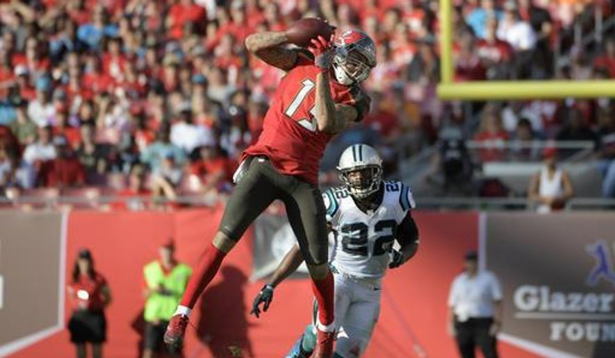FILE - In this Jan. 1, 2017, file photo, Tampa Bay Buccaneers wide receiver Mike Evans (13) catches a pass in front of Carolina Panthers free safety Michael Griffin (22) during the second half of an NFL football game in Tampa, Fla. Evans wants no part of a debate about whether he or New York Giants' Odell Beckham Jr., is the best young receiver in the NFL. (AP Photo/Phelan M. Ebenhack, File)