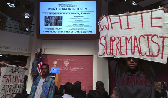 Protesters stand and hold signs and demonstrate during a speech by Education Secretary Betsy DeVos at Harvard University's Kennedy School of Government in Cambridge, Thursday. Sept. 28, 2017. She did not interrupt her speech to address the protesters, but later took some pointed questions from the audience. Asked about protections for transgender student, DeVos said she is committed to making sure all students are safe. Earlier this year, she rescinded guidance that allowed transgender students to use bathrooms that matched their gender identity. (AP Photo/Maria Danilova)