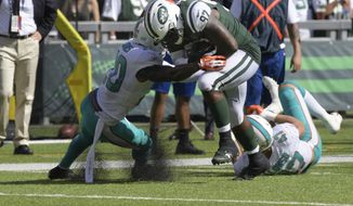 FILE - In this Sunday, Sept. 24, 2017, file photo, New York Jets' Lawrence Thomas (97) tackled by Miami Dolphins' Reshad Jones (20) during the second half of an NFL football game in East Rutherford, N.J. Thomas was the New York Jets' secret weapon last Sunday when the defensive lineman lined up at fullback, and even caught a pass and nearly scored. (AP Photo/Bill Kostroun, File)