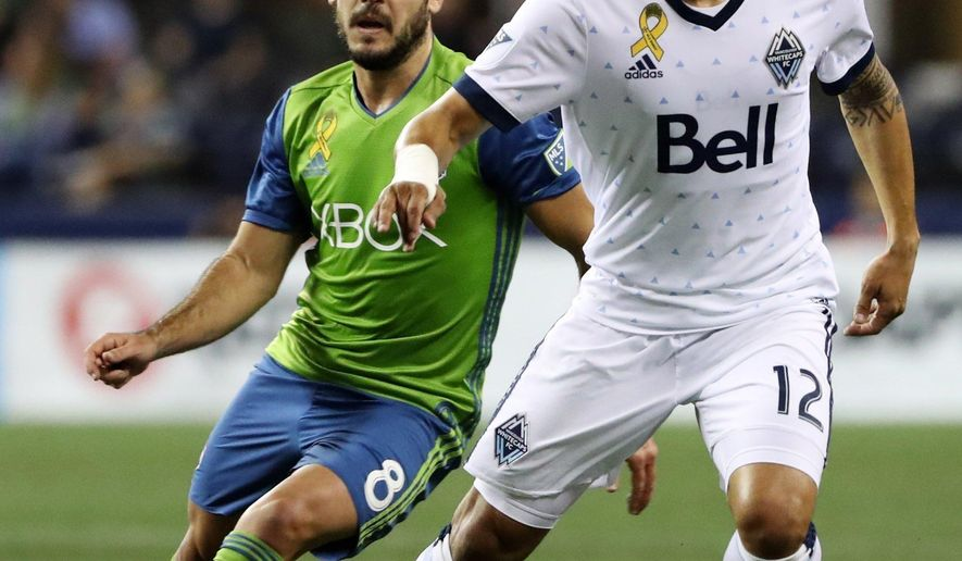 Seattle Sounders' Victor Rodriguez (8) guards Vancouver Whitecaps' Fredy Montero (12)  during the first half of an MLS soccer match in Seattle on Wednesday, Sept. 27, 2017. (Erika Schultz/The Seattle Times via AP)