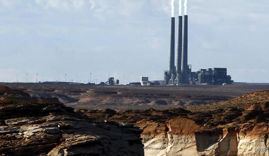 FILE - In this Sept. 4, 2011 file photo, smoke rises from the stacks of the main plant facility at the Navajo Generating Station, as seen from Lake Powell in Page, Ariz. The coal-fired power plant in far northern Arizona that was built to deliver water to the state's desert region is set to retire in 2019 unless a new owner can be found. (AP Photo/Ross D. Franklin, File)