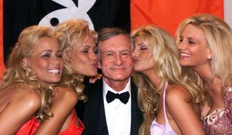 FILE - In this May 14, 1999 file photo, Playboy founder and editor in chief Hugh Hefner receives kisses from Playboy playmates during the 52nd Cannes Film Festival in Cannes, France. Hefner has died at age 91. The magazine released a statement saying Hefner died at his home in Los Angeles of natural causes on Wednesday night, Sept. 27, 2017, surrounded by family. (AP Photo/Laurent Rebours, File)
