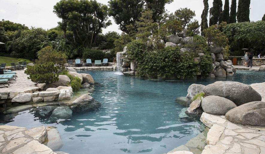FILE - This May 11, 2016 file photo shows the pool area at the Playboy Mansion in Los Angeles. Hugh Hefner bought the Holmby Hills property in 1971 and turned it into the epicenter of his growing magazine and lifestyle enterprise. A neighbor bought the property for $100 million in 2016 with the stipulation that Hefner could live the rest of his years there. He died Wednesday at 91. (Photo by John Salangsang/Invision/AP, File)