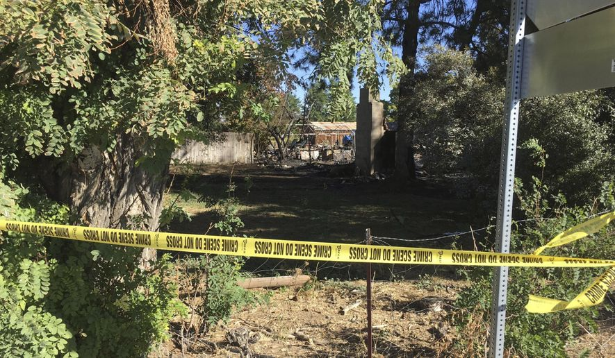 In this photo released by the Ada County Sheriff's Office, crime tape seals off a home that burned overnight Thursday, Sept 28, 2017, in Meridian, Idaho. Idaho authorities responding to a home invasion Wednesday night shot at the suspect who ran back inside the house minutes before it caught fire, leaving two people injured and at least one person dead. Police are uncertain if the suspect was still in the house as it burned down. (Ada County Sheriff's Office via AP)