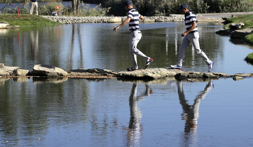 Justin Thomas, left, and Rickie Fowler, right, walks to the 13th hole during the Presidents Cup foursomes golf matches at Liberty National Golf Club in Jersey City, N.J., Thursday, Sept. 28, 2017. (AP Photo/Julio Cortez)