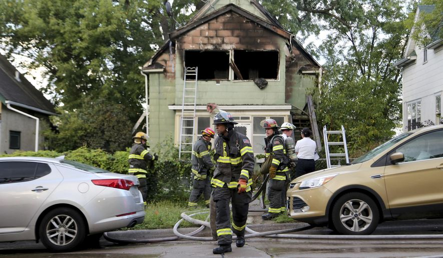 Firefighters look over the scene of a duplex fire that gutted the upstairs and left two seriously burned Thursday, Sept. 28, 2017, in Minneapolis.   Police say a woman was critically burned when a man set her on fire in a domestic dispute that also left him with severe burns.  (David Joles/Star Tribune via AP)