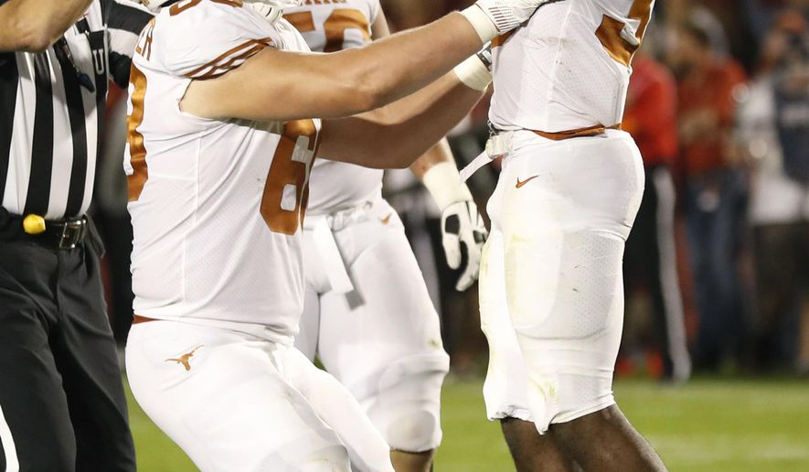 Texas running back Toneil Carter, right, celebrates with teammates after catching a touchdown pass during the first half of an NCAA college football game against Iowa State, Thursday, Sept. 28, 2017, in Ames, Iowa. (AP Photo/Charlie Neibergall)