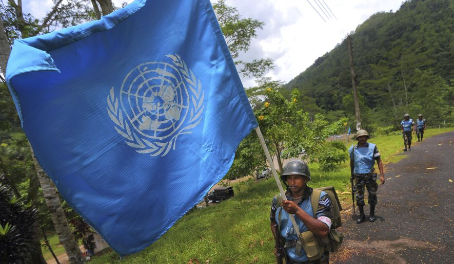 FILE - In this Sept. 13, 2016 photo, a Sri Lanka Air Force airman carries the U.N. flag during training for a road patrol at the Institute of Peace Support Operations Training in Kukuleganga, Sri Lanka. A U.N. fund to help victims of sexual abuse and exploitation by peacekeepers and U.N. staff has now grown to $1.5 million following contributions from 10 more countries including Sri Lanka, whose troops were implicated in a three-year-long child sex ring in Haiti. The U.N. Department of Field Support made the announcement Thursday, Sept. 28, 2017 in New York. (AP Photo/Eranga Jayawardena, file)