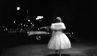 This 1957 photo provided by the Estate of Vivian Maier and John Maloof Collection a woman in a party dress walking towards a car in Miami. New research about Maier shows the enigmatic Chicago nanny was obsessive about honing her skills as a photographer starting in 1950. (Vivian Maier/Estate of Vivian Maier and John Maloof Collection via AP)