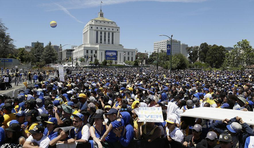 FILE - In this June 15, 2017 file photo, people fill a plaza at the Henry J. Kaiser Convention Center to watch the Golden State Warriors' NBA championship rally in Oakland, Calif. Oakland officials say the Golden State Warriors made good on their word and have refunded the city almost $800,000 spent to host the team's 2017 Championship parade. (AP Photo/Eric Risberg, File)