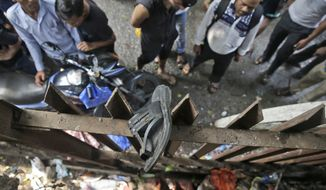 A slipper of an injured commuter is seen stuck on the railing of a pedestrian bridge where a stampede took place at the Elphinstone station, in Mumbai, India, Friday, Sept. 29, 2017. The stampede broke out on a crowded pedestrian bridge connecting two railway stations in Mumbai during the Friday morning rush, killing a number of people police said. (AP Photo/Rafiq Maqbool)