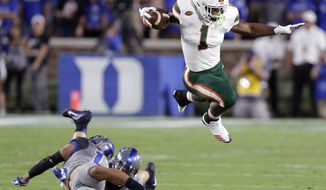 Miami's Mark Walton, right, jumps over Duke's Ben Humphreys and Bryon Fields Jr. during the first half of an NCAA college football game in Durham, N.C., Friday, Sept. 29, 2017. (AP Photo/Gerry Broome)