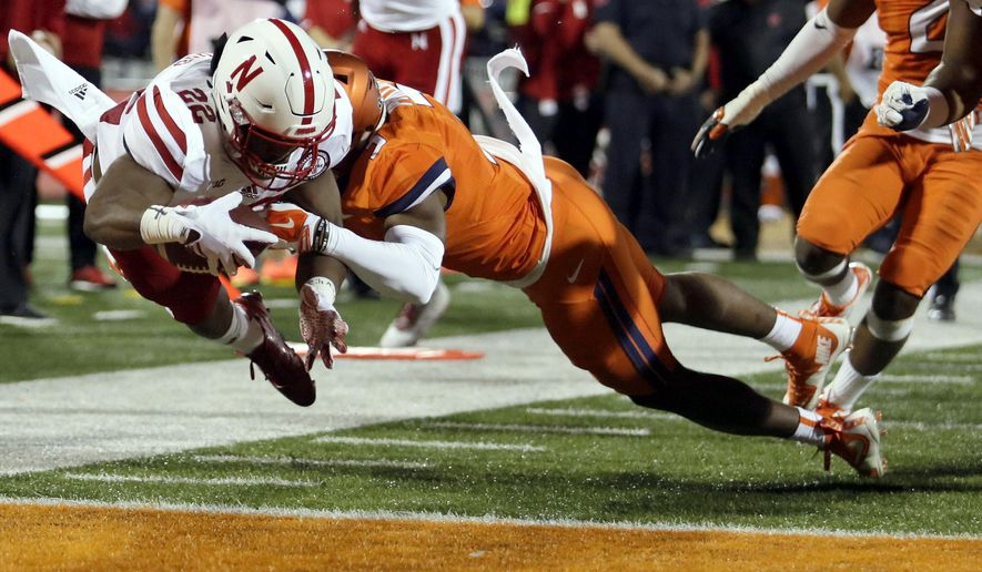Nebraska running back Devine Ozigbo (22) dives into the end zone for a touchdown against Illinois linebacker Del'Shawn Phillips (3) during the first half of an NCAA college football game Friday, Sept. 29, 2017, in Champaign, Ill. (AP Photo/Stephen Haas)
