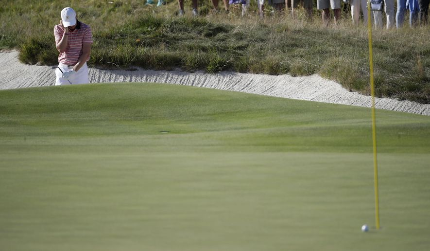 Justin Thomas reacts after missing a shot from a bunker on the 16th hole during the four-ball golf matches on the second day of the Presidents Cup at Liberty National Golf Club in Jersey City, N.J., Friday, Sept. 29, 2017. (AP Photo/Julio Cortez)