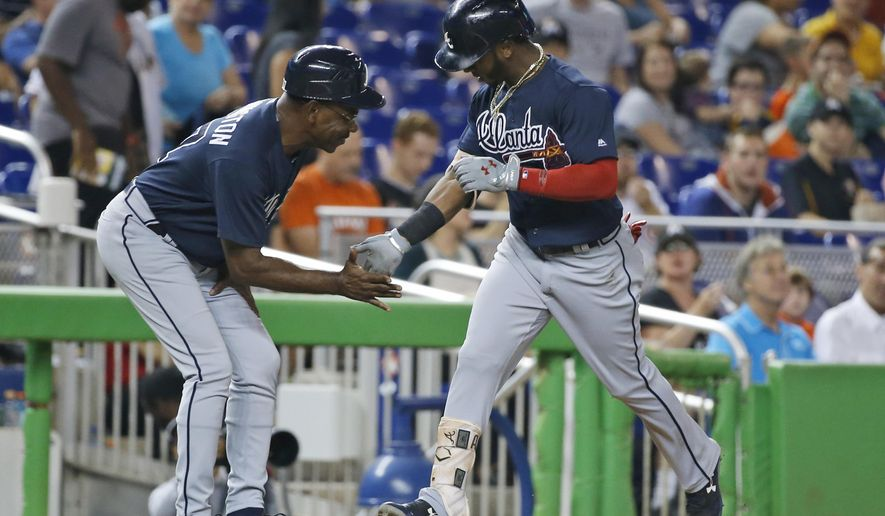 Atlanta Braves' Ozzie Albies, right, is congratulated by third base coach Ron Washington as Albies heads for home after hitting a home run during the first inning of a baseball game against the Miami Marlins, Friday, Sept. 29, 2017, in Miami. (AP Photo/Wilfredo Lee)