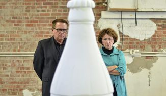 In this Thursday, Sept. 28, 2017 photo, Greg Greiner, one of the Coca-Cola Contour Bottle sponsors, and Annalee Chalos-McAleese, the artist that will design Greiner's bottle, look over the blank canvas during an event at the former Mace Ford building in Terre Haute, Ind. (Austen Leake /The Tribune-Star via AP)