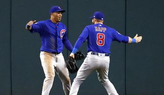 Chicago Cubs center fielder Leonys Martin, left, is congratulated by Ian Happ after Martin caught a ball at the outfield wall hit by St. Louis Cardinals' Paul DeJong to end a baseball game during the 11th inning Thursday, Sept. 28, 2017, in St. Louis. The Cubs won 2-1. (AP Photo/Jeff Roberson)