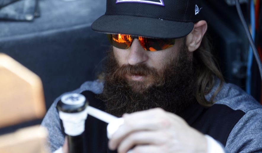 Colorado Rockies center fielder Charlie Blackmon tapes the handle of his bat before a baseball game against the Los Angeles Dodgers, Friday, Sept. 29, 2017, in Denver. (AP Photo/David Zalubowski)