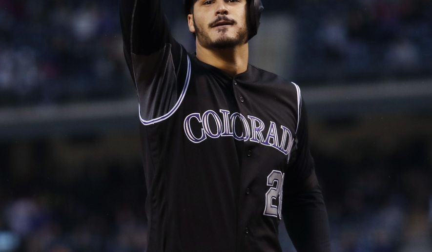 Colorado Rockies' Nolan Arenado gestures to the crowd after hitting a solo home run off Los Angeles Dodgers starting pitcher Hyun-Jin Ryu in the first inning of a baseball game Friday, Sept. 29, 2017, in Denver. (AP Photo/David Zalubowski)