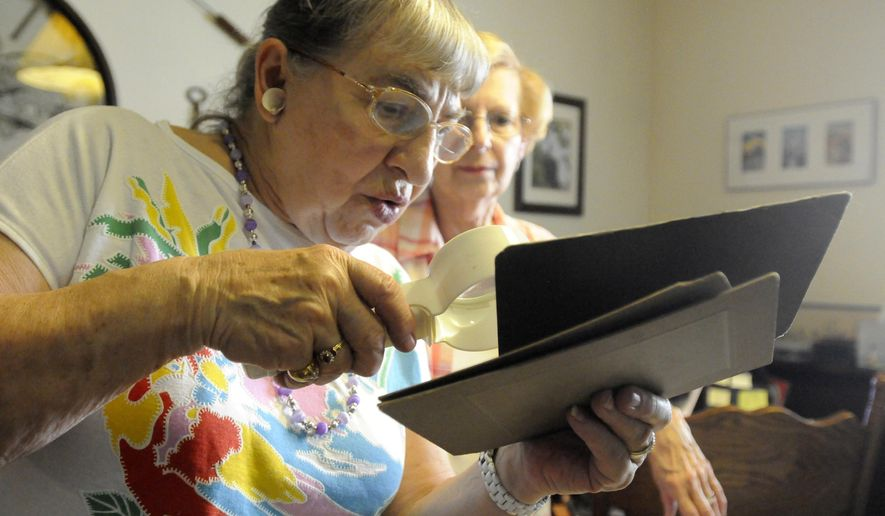 In this Aug. 30, 2017 photo, Kankakee Valley Genealogical Society member Nelda Ravens, left, examine the fine print on a photograph.as Marcia Stang, the society's president,  estimates the photo to be from the early 1900's during the organization's weekly meeting. Founded in 1968, Kankakee Valley Genealogical Society society pre-dates genealogy giant ancestry.com, a website which has more than 2.6 million paying users. Instead, these history detectives work the old-fashioned way, combing through church records, obituaries, graveyards and more to put the missing pieces of the past back together. The search never ends. (Tiffany Blanchette/The Daily Journal via AP)
