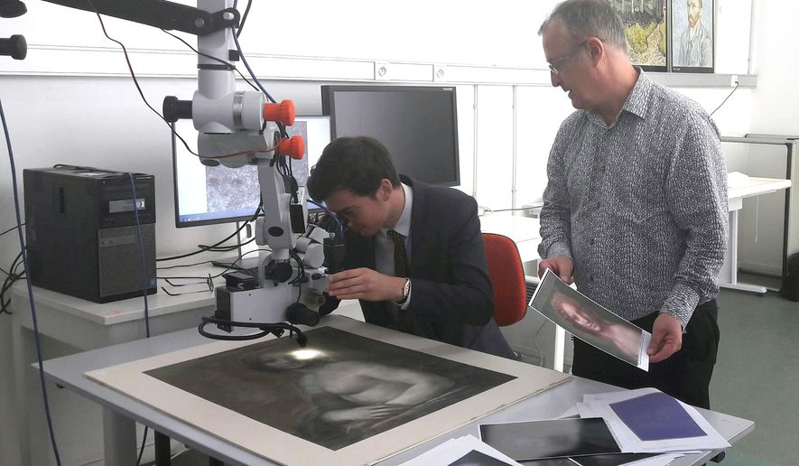 In this photo provided by the Conde museum, Chateau de Chantilly, and dated Wednesday, Sept. 27, 2017, chief curator of heritage, Bruno Mottin, left, examines a charcoal sketch through a microscope, depicting a nude woman while Mathieu Deldicque, curator at Conde museum, looks on, at the Center for Research and Restoration of the Museums of France in Paris, France. There's something vaguely familiar about this charcoal sketch of a woman's face and nude torso _ could it be an unclothed precursor to the Mona Lisa? (Domaine de Chantilly via AP)