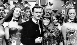 FILE - In this Sept. 5, 1969, file photo, Hugh Hefner, publisher and owner of Playboy Magazine, and his girlfriend Barbara Benton, 19-year-old coed turned actress, are surrounded by Bunny Girls at the Playboy Club in London. Playboy magazine founder and sexual revolution symbol Hefner has died at age 91. The magazine released a statement saying Hefner died at his home of natural causes on Wednesday night, Sept. 27, 2017, surrounded by family. (AP Photo/FIle)
