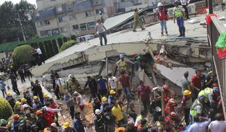 FILE- In this Sept. 19, 2017 file photo, rescue workers search for children trapped inside the collapsed Enrique Rebsamen school in Mexico City. Authorities said that the owner of the privately owned Enrique Rebsamen school built an apartment for herself on top of the collapsed wing, which local media said included a Jacuzzi, and were looking into whether the extra weight may have played a role in the collapse. (AP Photo/Carlos Cisneros, File)