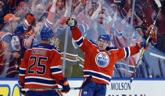 FILE - In this April 14, 2017, file photo, Edmonton Oilers' Darnell Nurse (25) and Connor McDavid (97) celebrate a goal against the San Jose Sharks during the third period of Game 2 of an NHL hockey Stanley Cup first-round playoff series, in Edmonton, Alberta. McDavid's eight-year, $100 million contract is the latest and most eye-popping example of a shift in priority by NHL teams intent on locking up their young stars. (Jason Franson/The Canadian Press via AP, File)